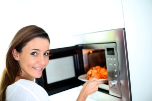 Woman putting plate in microwave oven