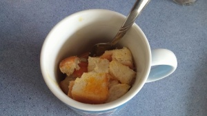 break the egg into the mug and mix with the bread pieces.
